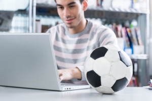 Man with football on desk